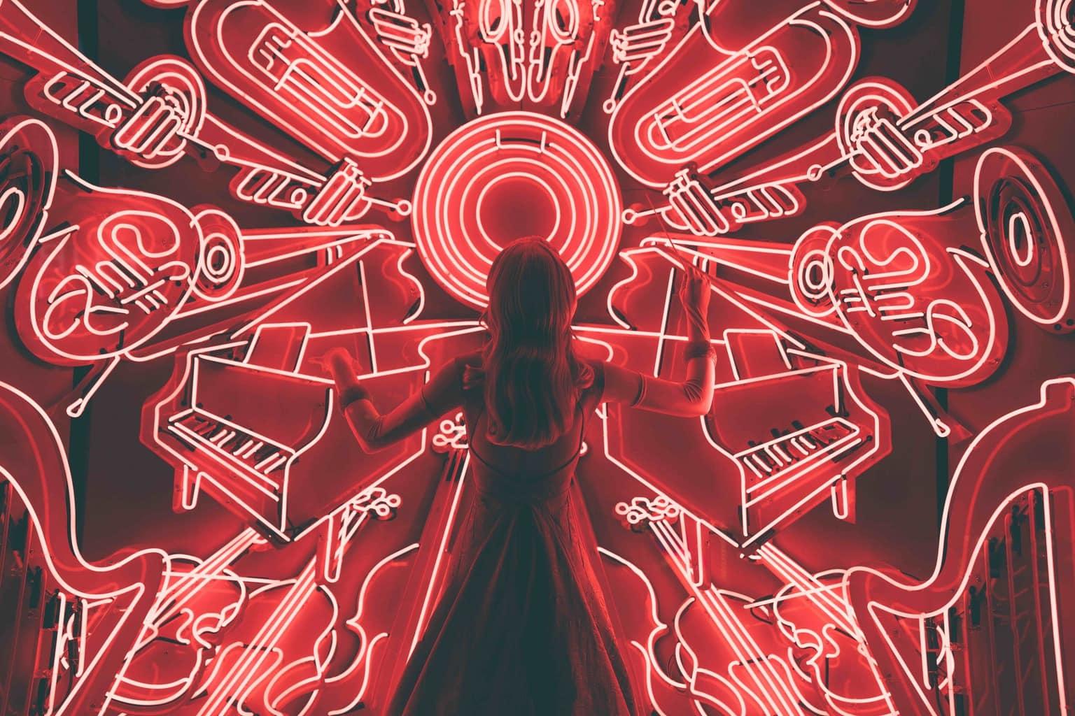 Letrero de neón rojo con chica delante como directora de orquesta