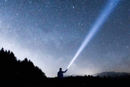cielo estrellado y silueta con linterna
