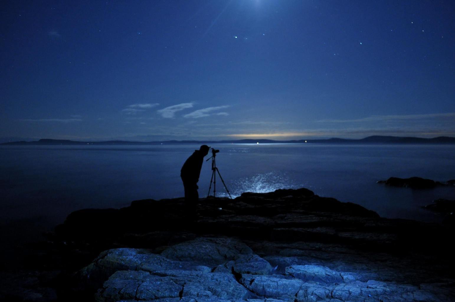 Fotógrafo con trípode en la costa fotografiando estrellas