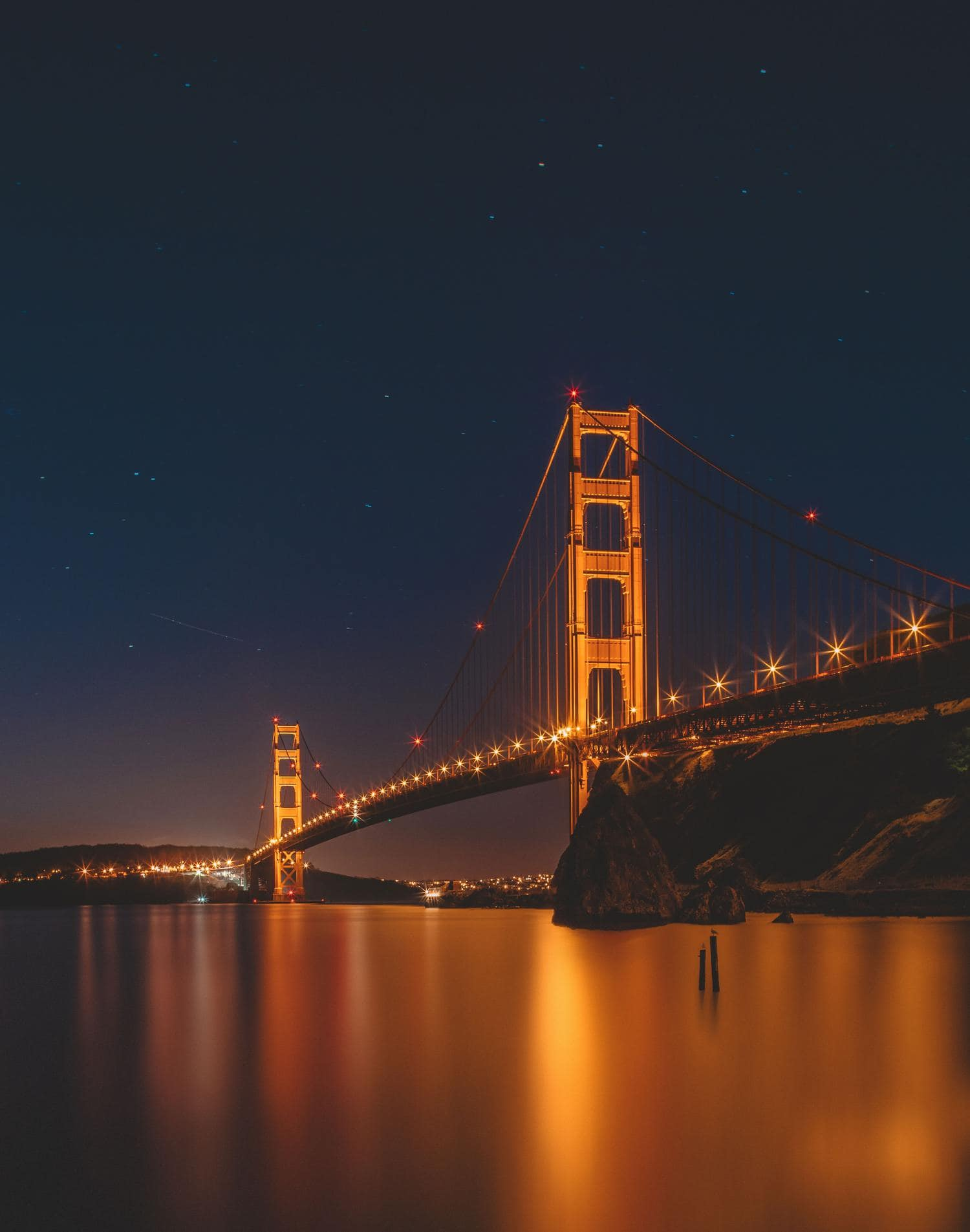 Puente como parte de un paisaje urbano nocturno con luz de farolas en forma de estrella