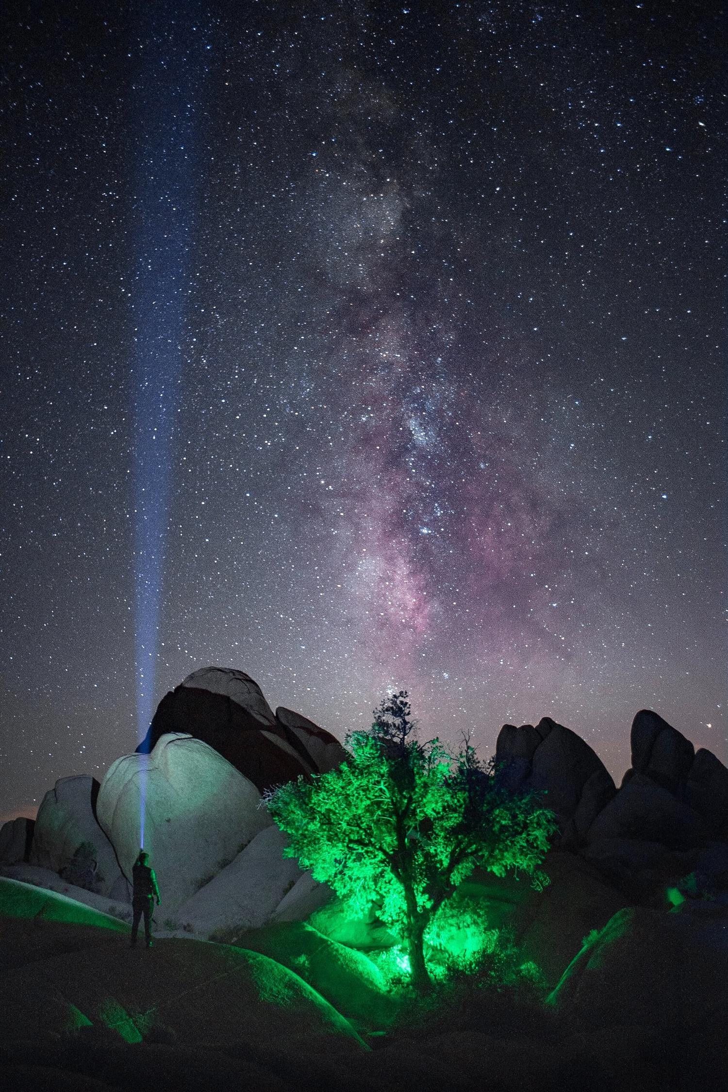 fotografía nocturna de cielo estrellado, haz de luz de linterna y flash con gel de color verde