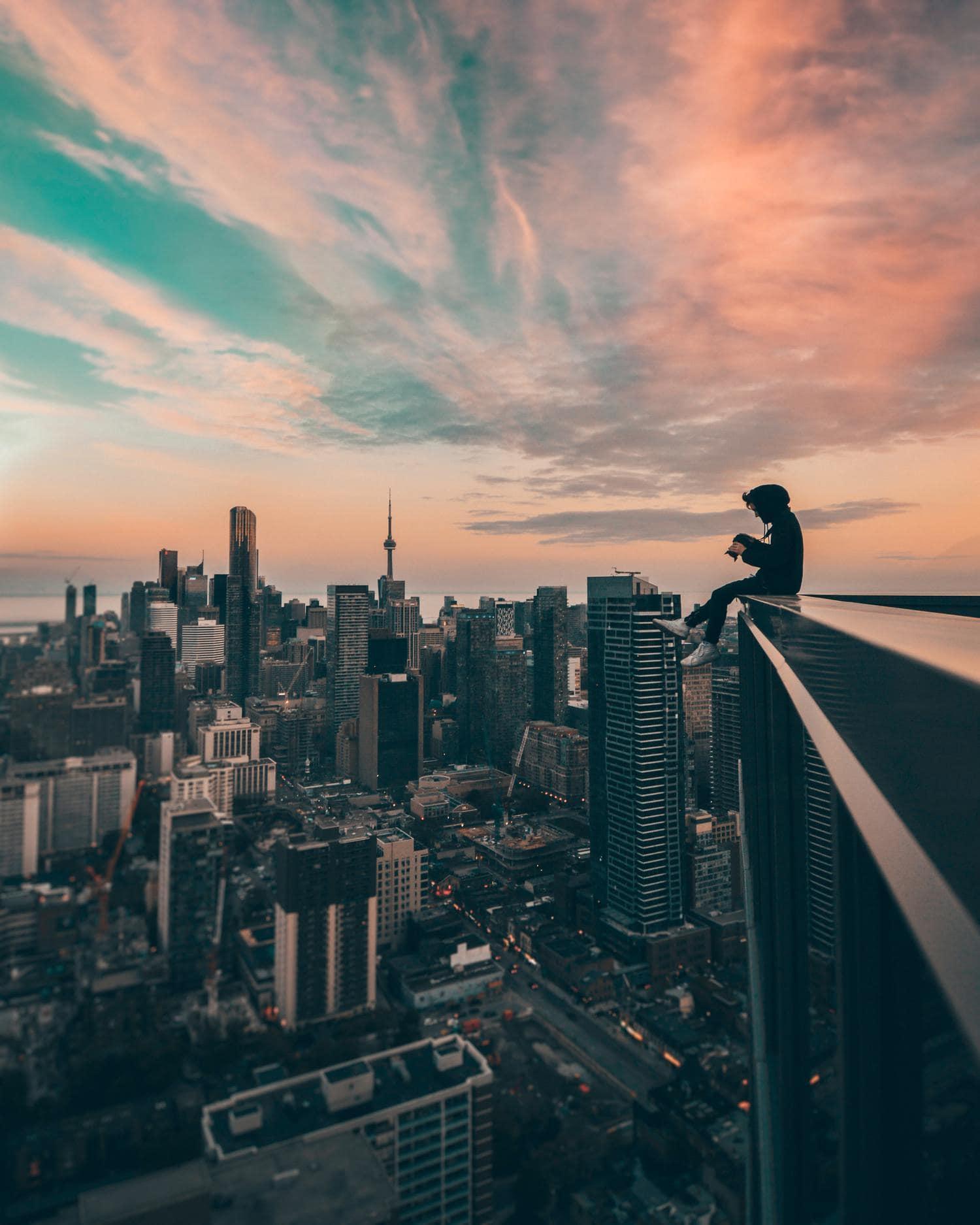 Fotógrafo en lo alto de un edificio con vistas de la urbe al fondo