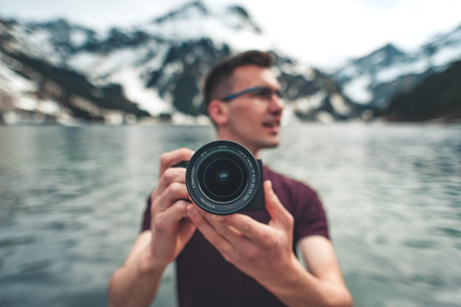 Fotógrafo con cámara en mano en medio naturaleza