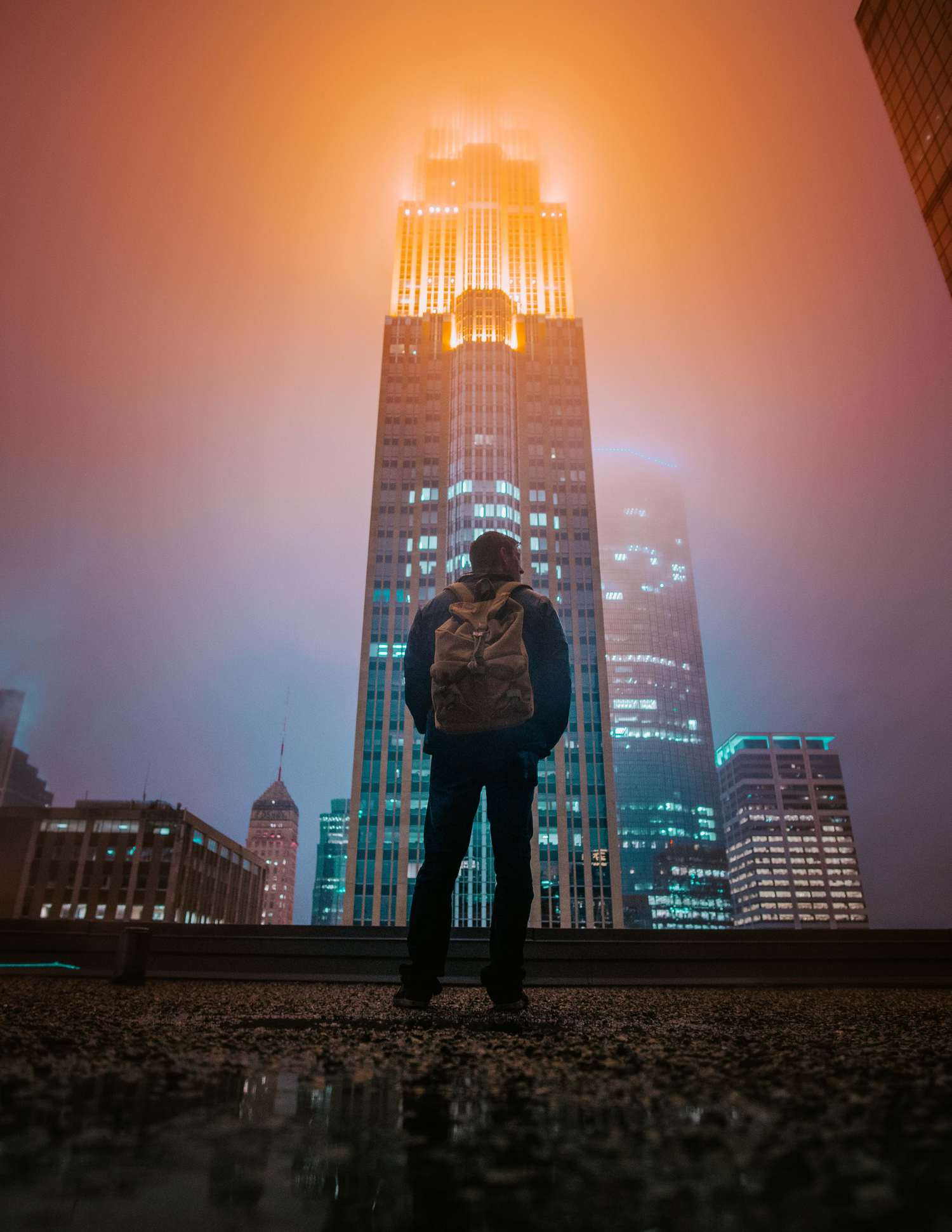 figura humana delante de rascacielos con luces encendidas
