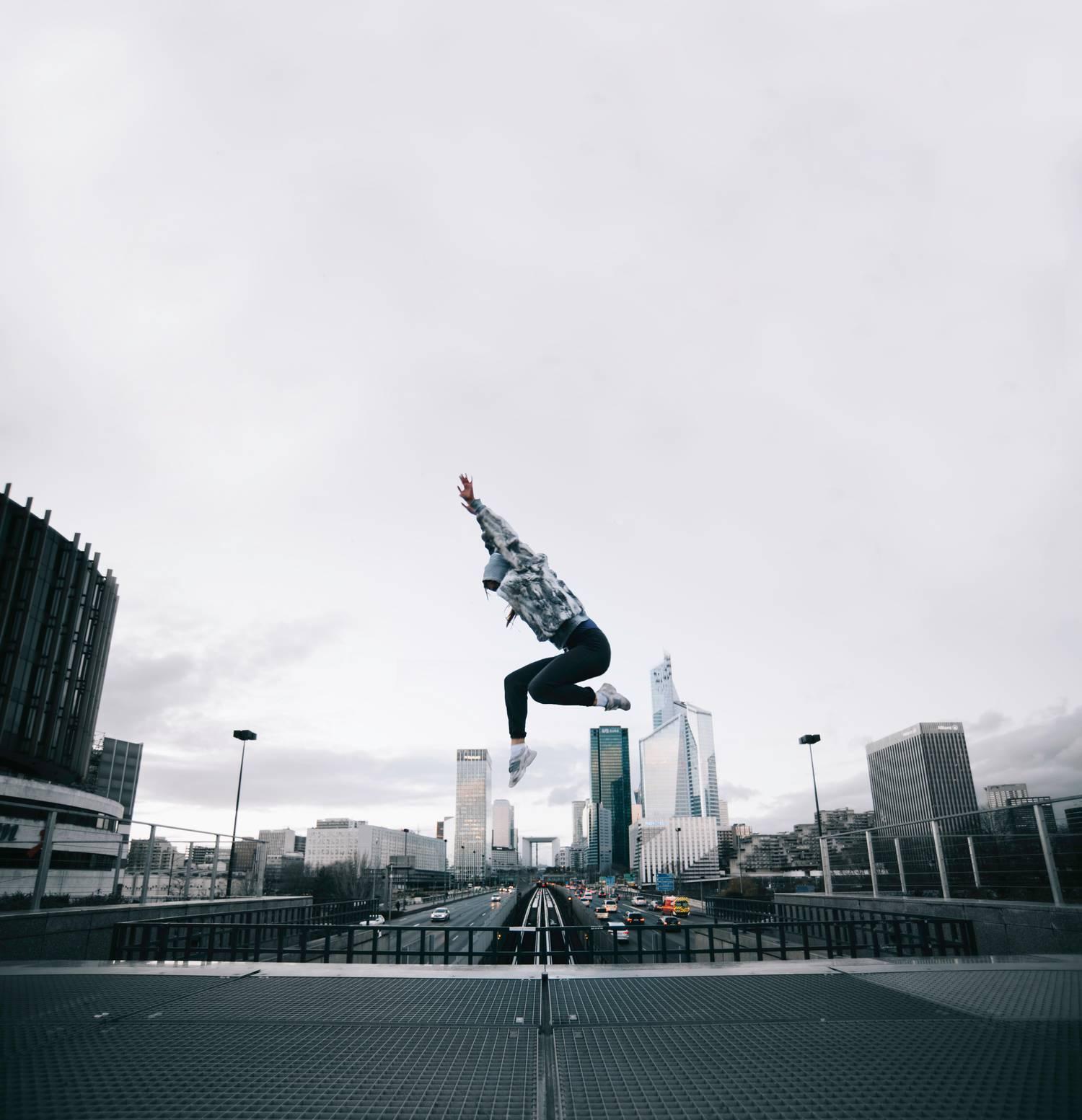 Joven saltando sobre la carretera y los rascacielos como ejemplo de fotografía urbana