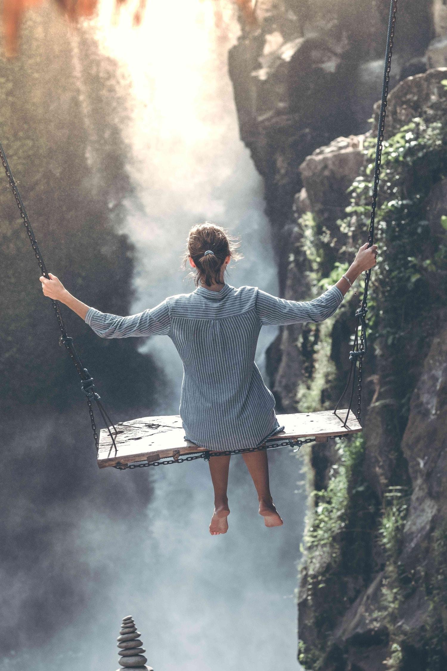 Mujer columpiándose sobre cascada, fotografía con alma
