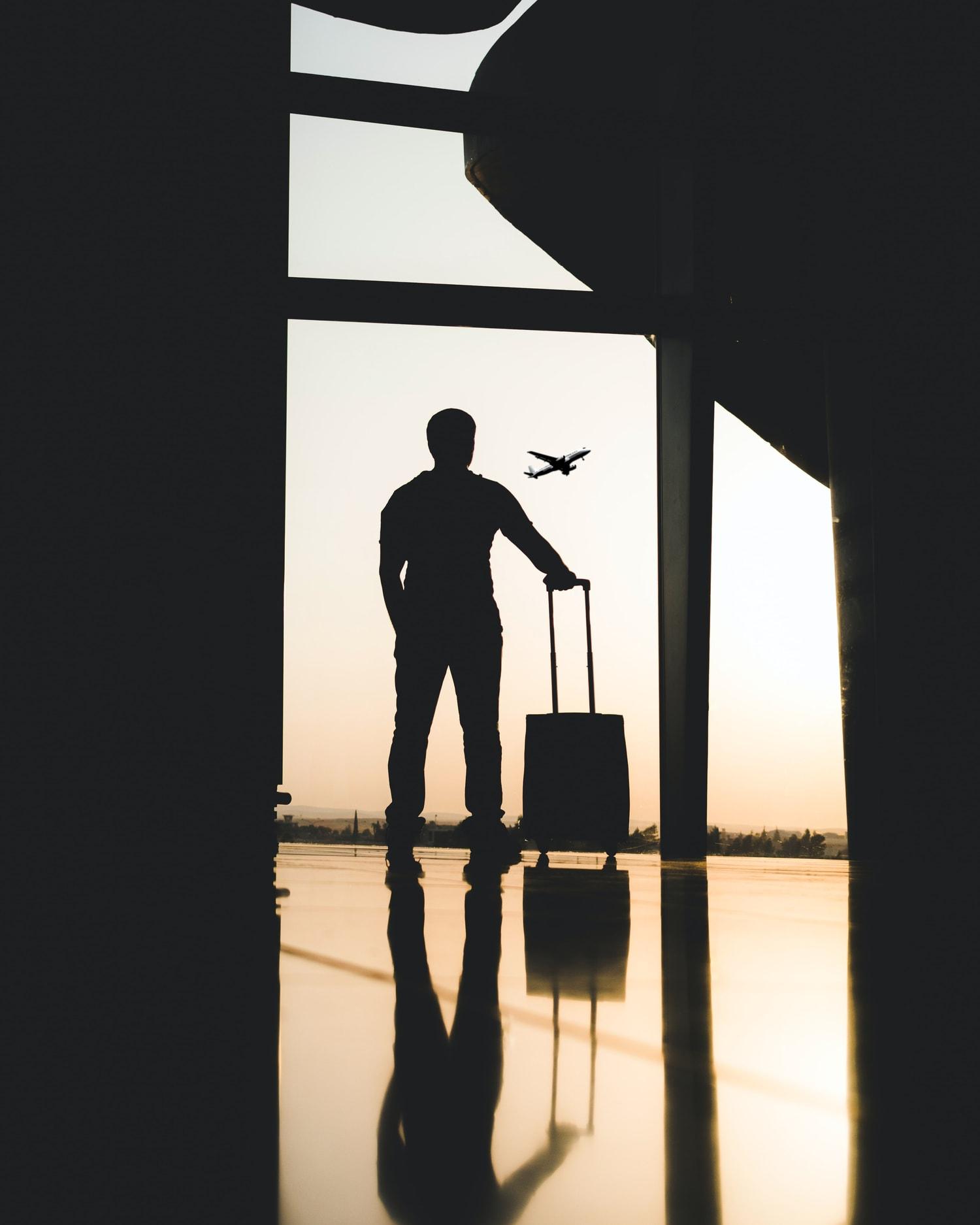 Hombre en aeropuerto viendo avión pasar