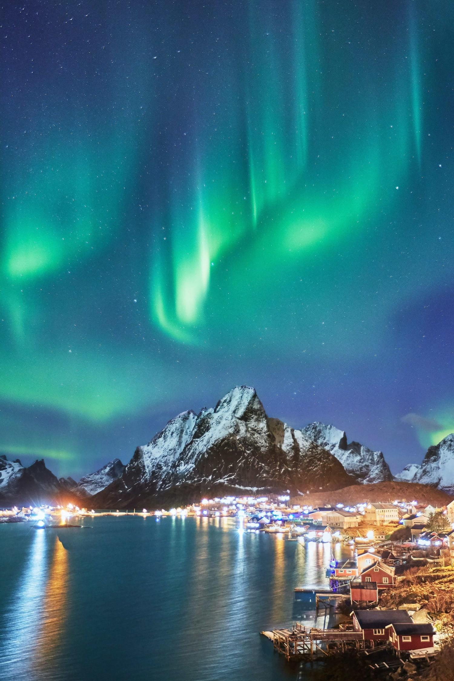 Aurora Boreal en pueblo de montaña nevado