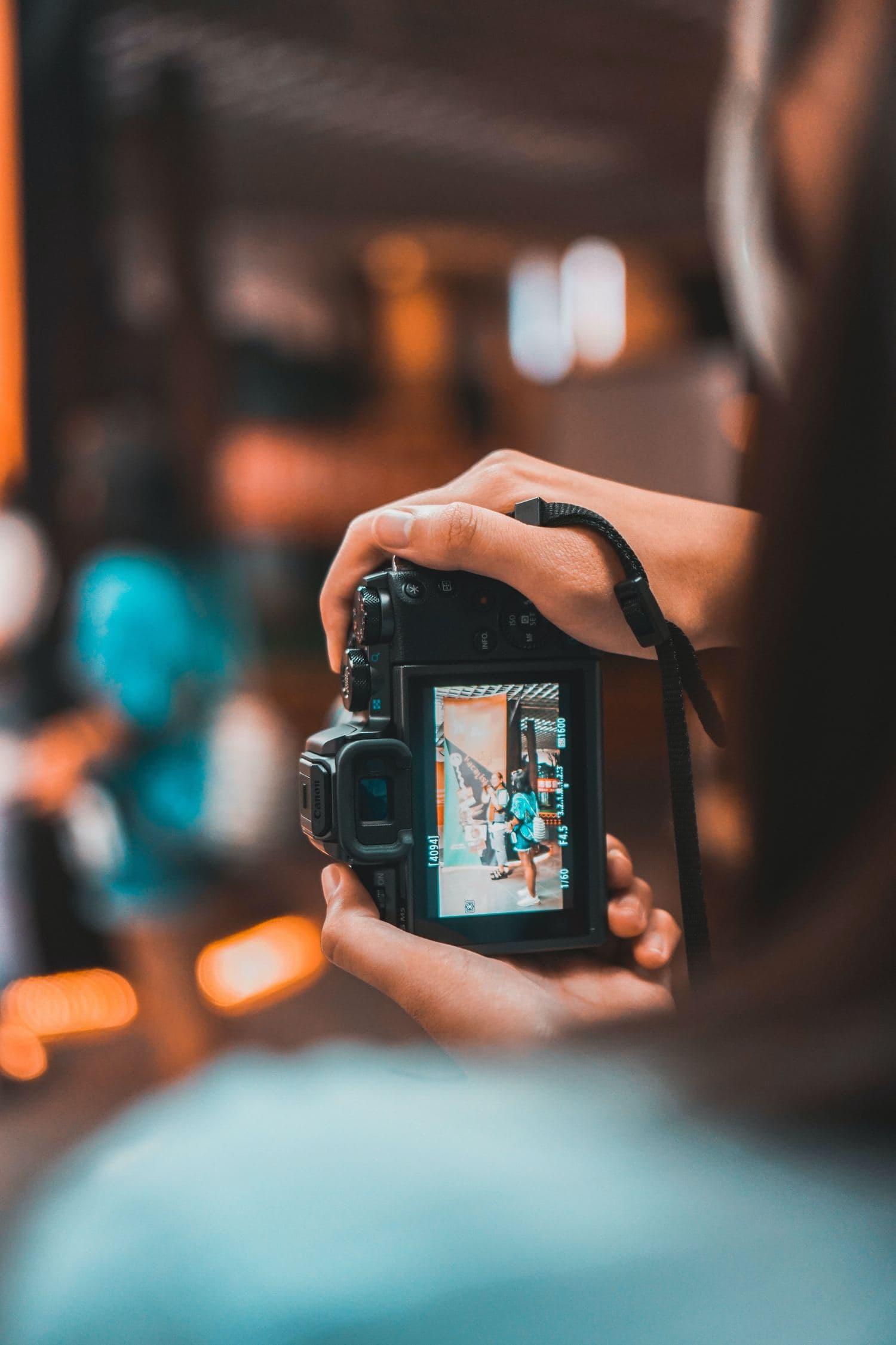 Cámara en mano de fotógrafa mientras elige la composición adecuada