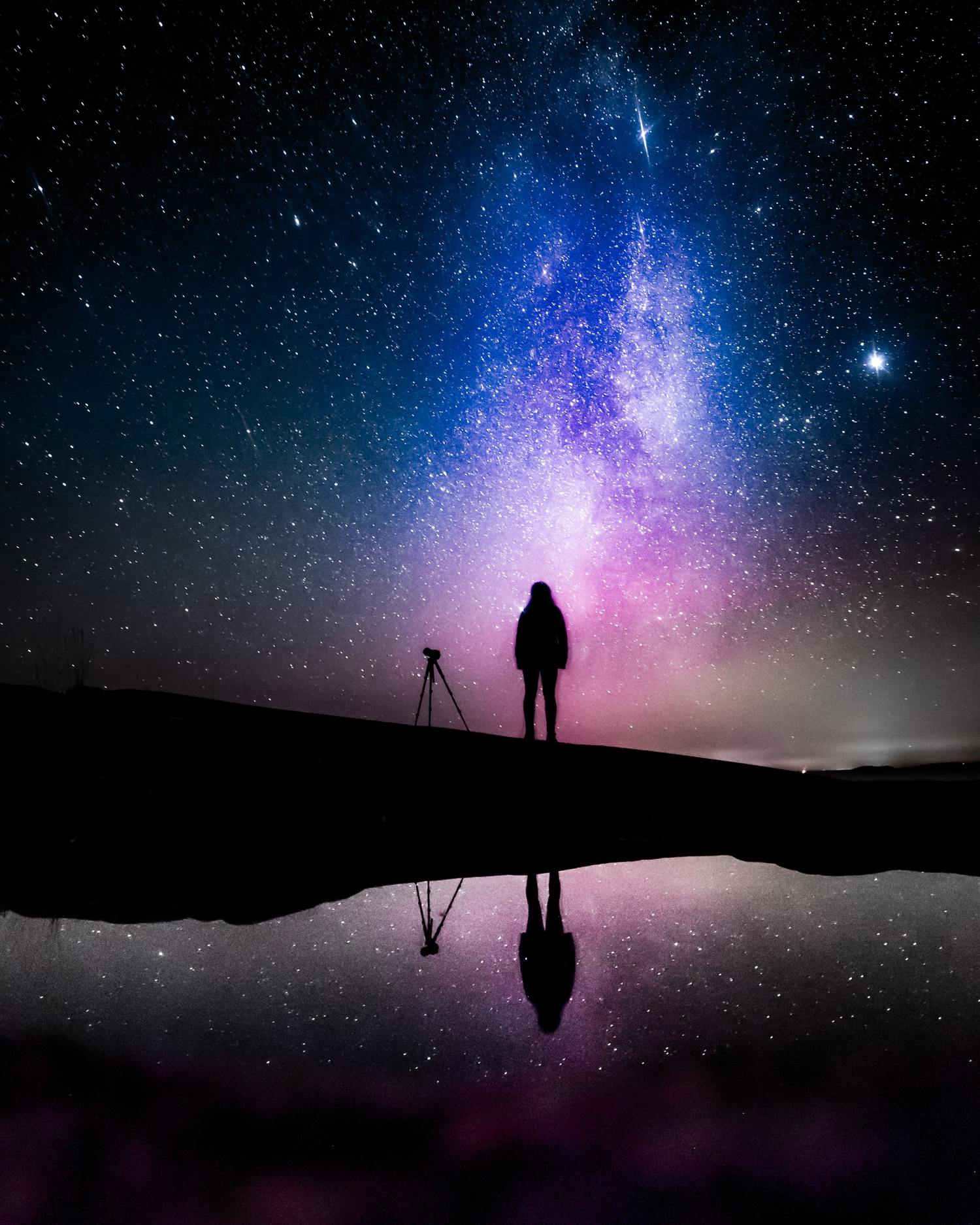 Silueta de fotógrafo con trípode con fondo de cielo estrellado