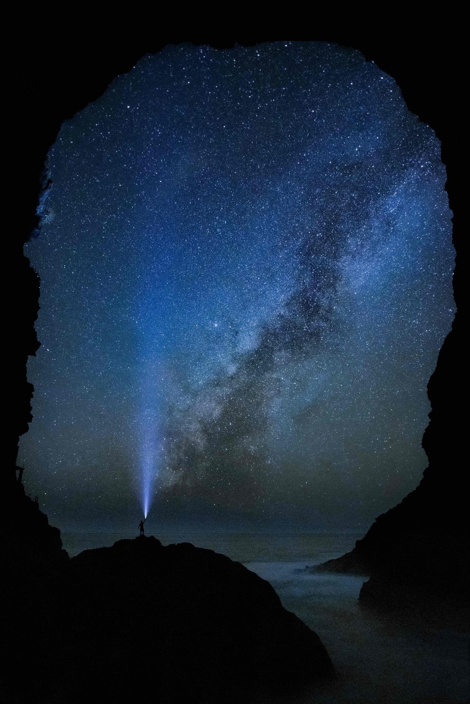 Hombrecito con luz de linterna y Vía Láctea de fondo