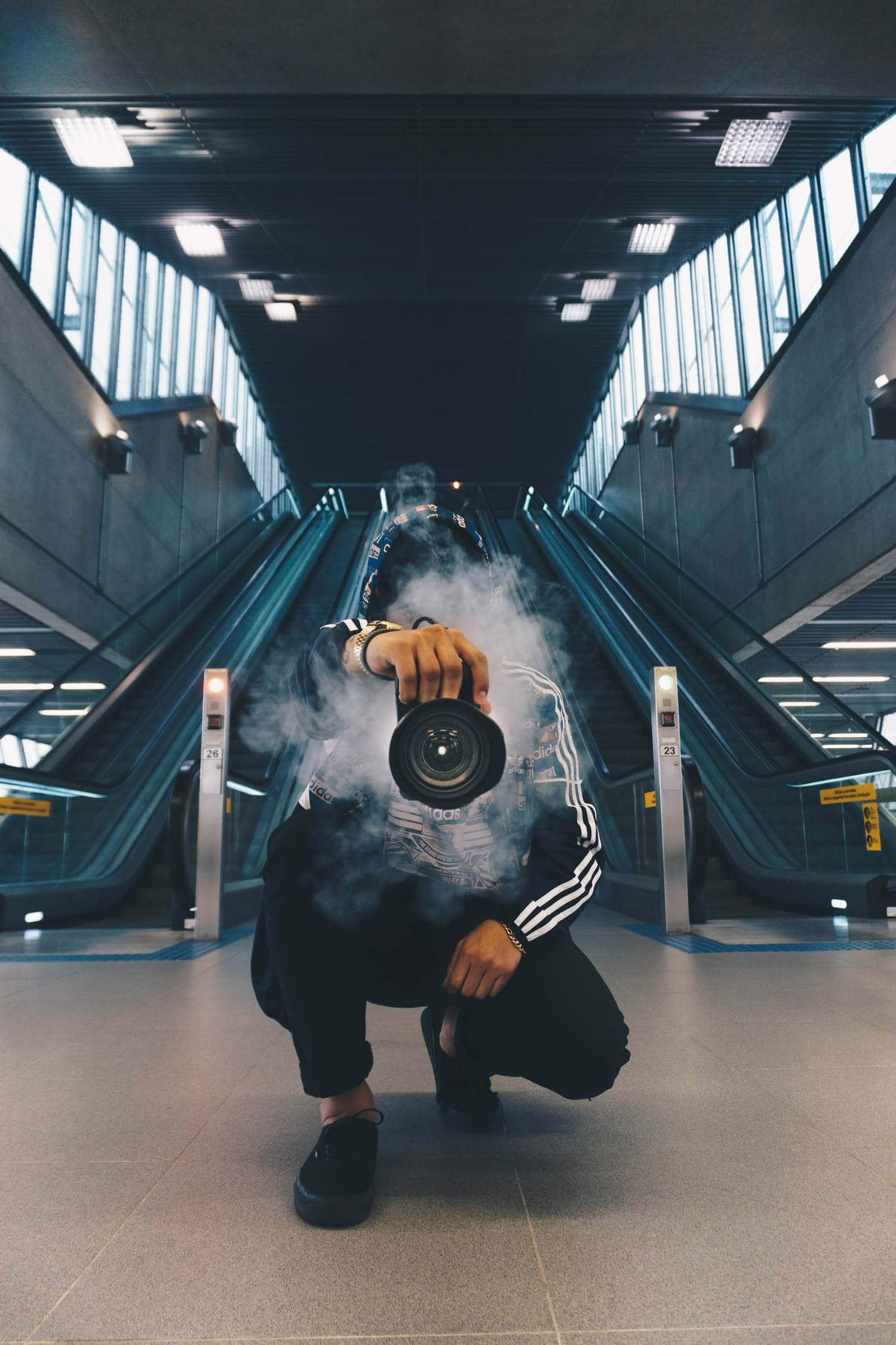 Fotógrafo con cámara en mano echando humo