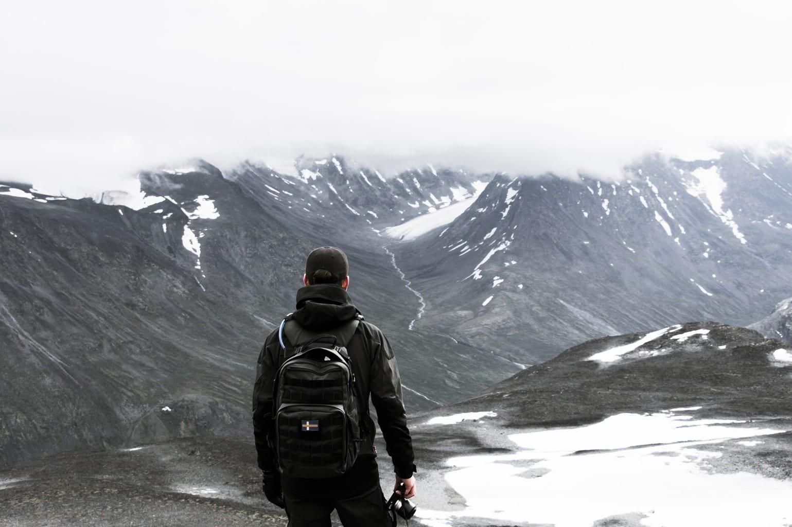 Fotógrafo en la nieve con mochila colgada a la espalda
