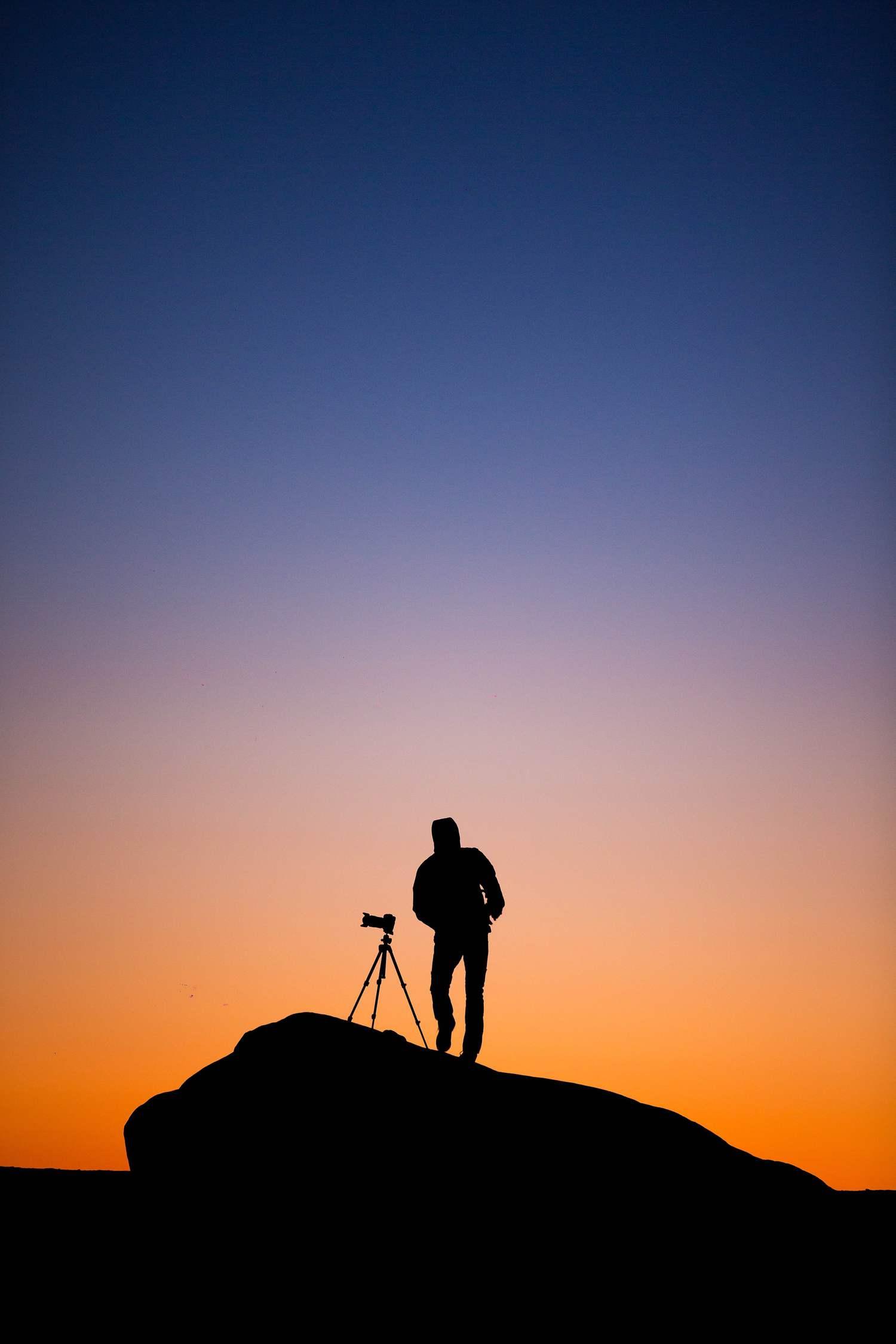 Silueta de fotógrafo nocturno en hora azul