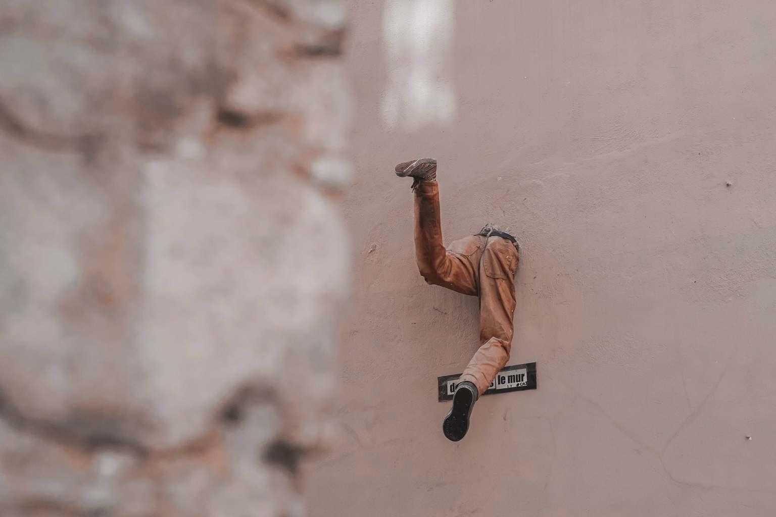 Mitad de un cuerpo asomando por un agujero de la pared