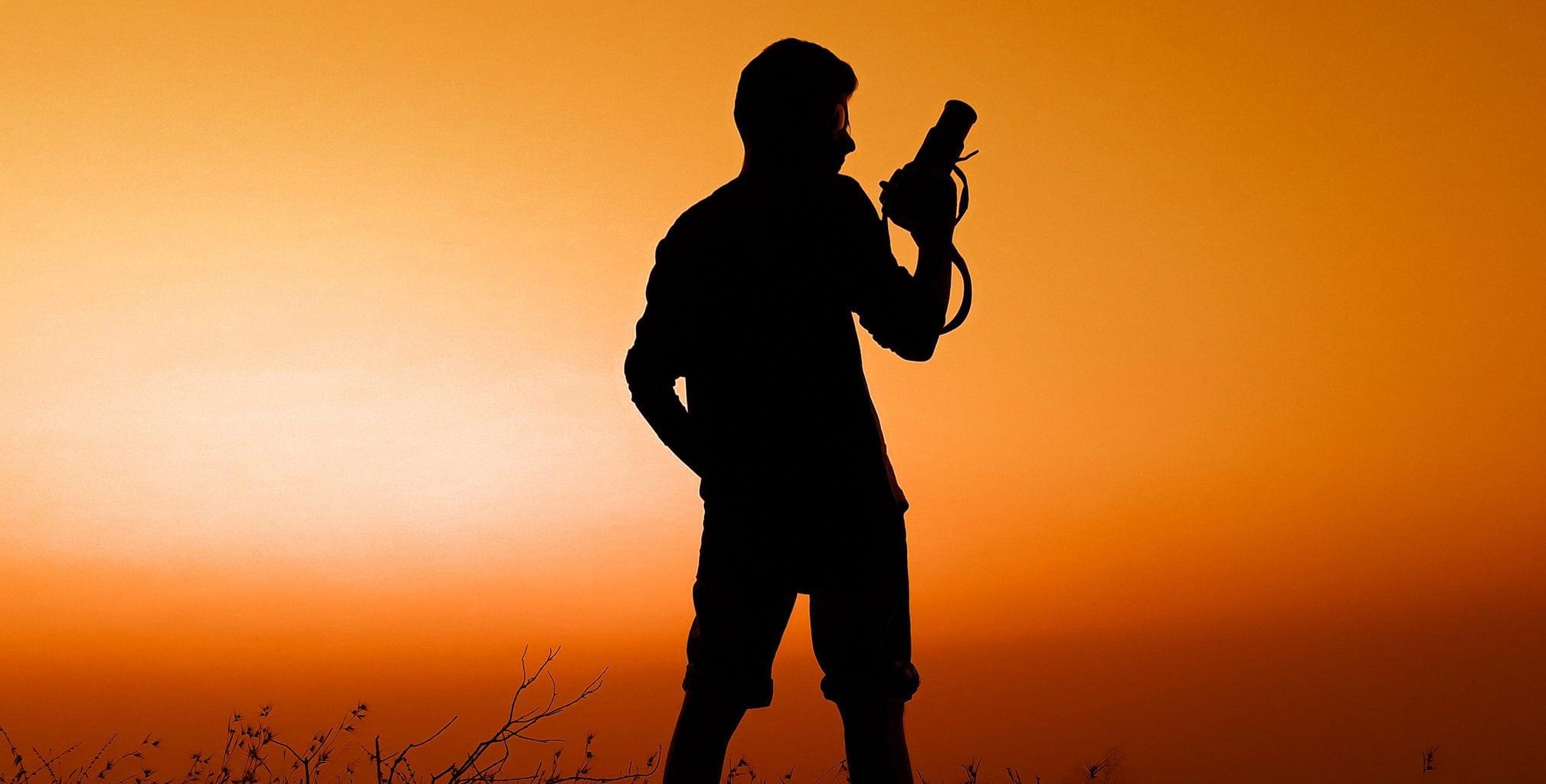 Silueta de fotógrafo con cámara en mano al atardecer