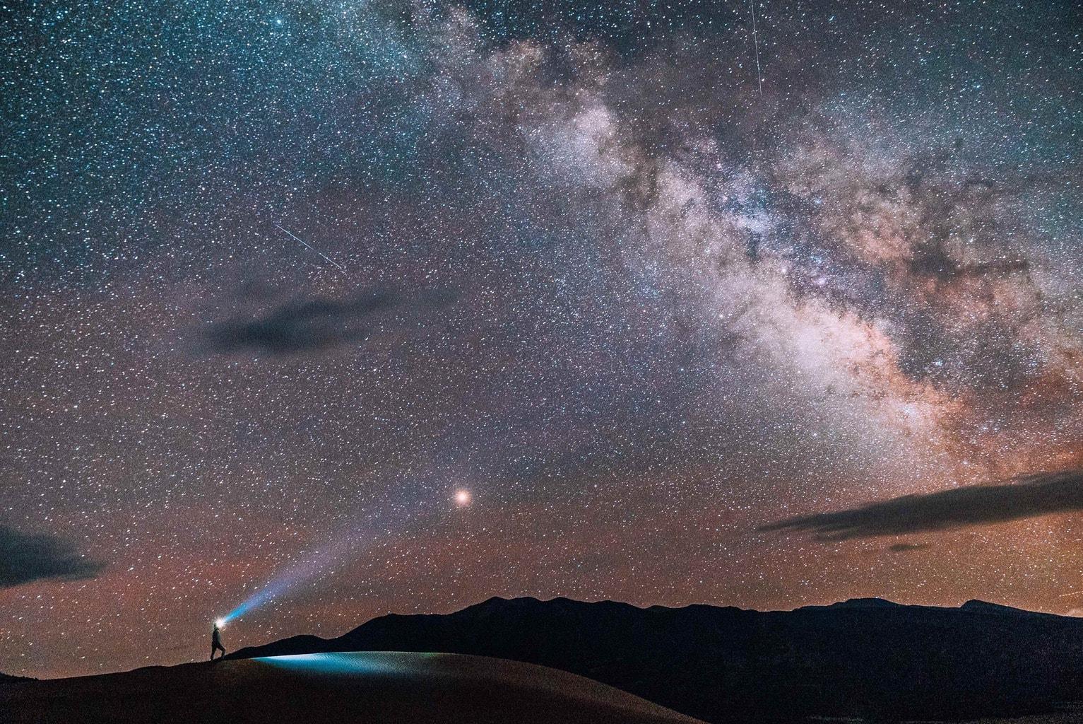 fotografía nocturna fotógrafo con linterna en montañas y estrellas y  vía láctea en el cielo