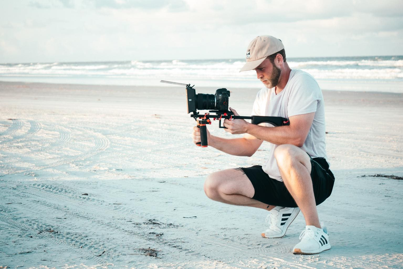 cámara vídeo playa hombre grabando