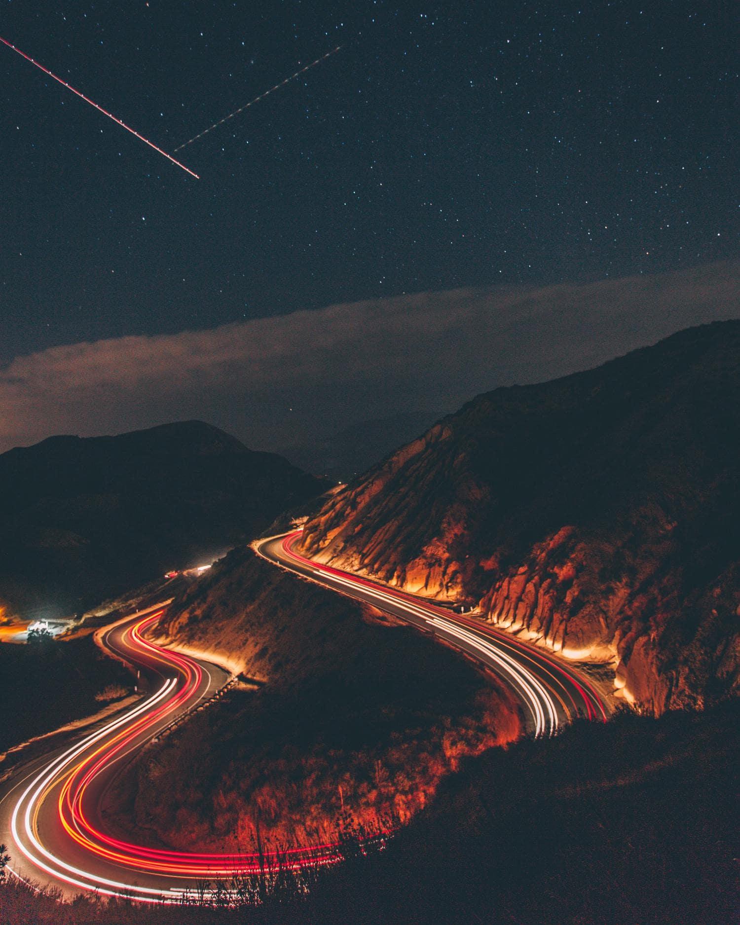 Estelas de luz de coches con estrellas de fondo en el cielo