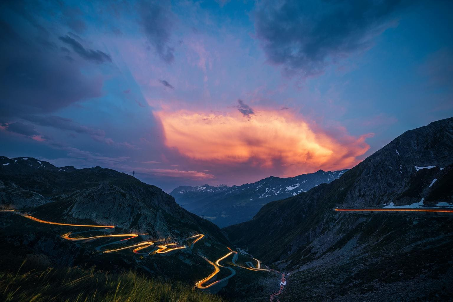 Estelas de luz en montañas con cielo de atardecer