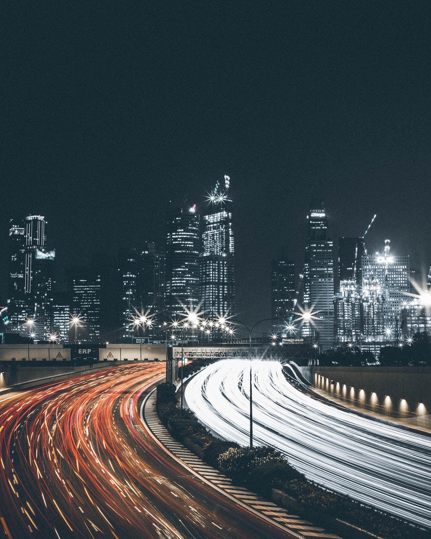 Estelas de luz en doble sentido con rascacielos de fondo