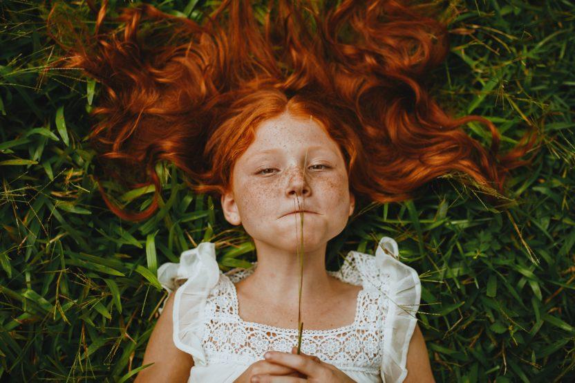 fotografía de niña tumbada en la hierba