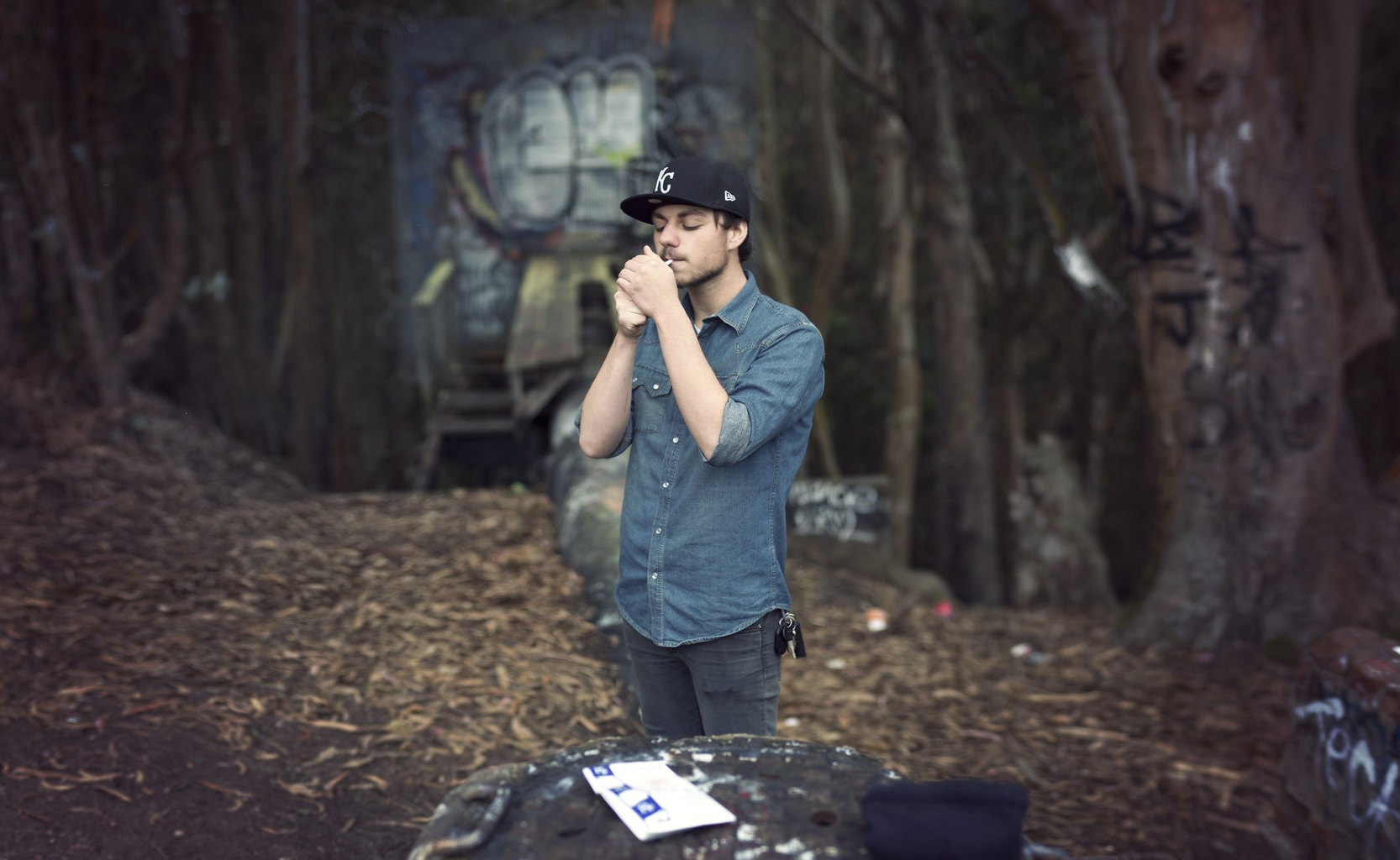 Joven fumando en el bosque fotografiado con el método Brenizer