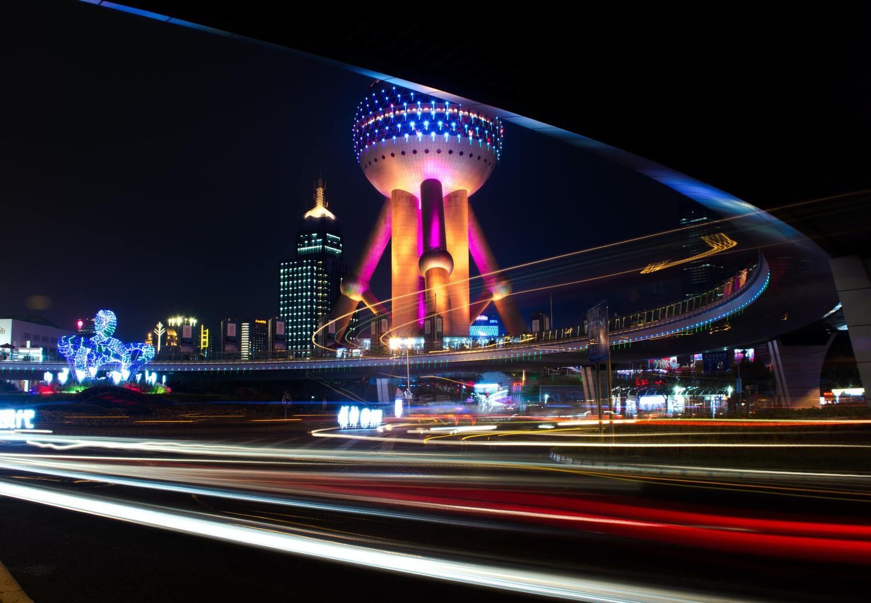 Estelas de luz con monumento iluminado de fondo