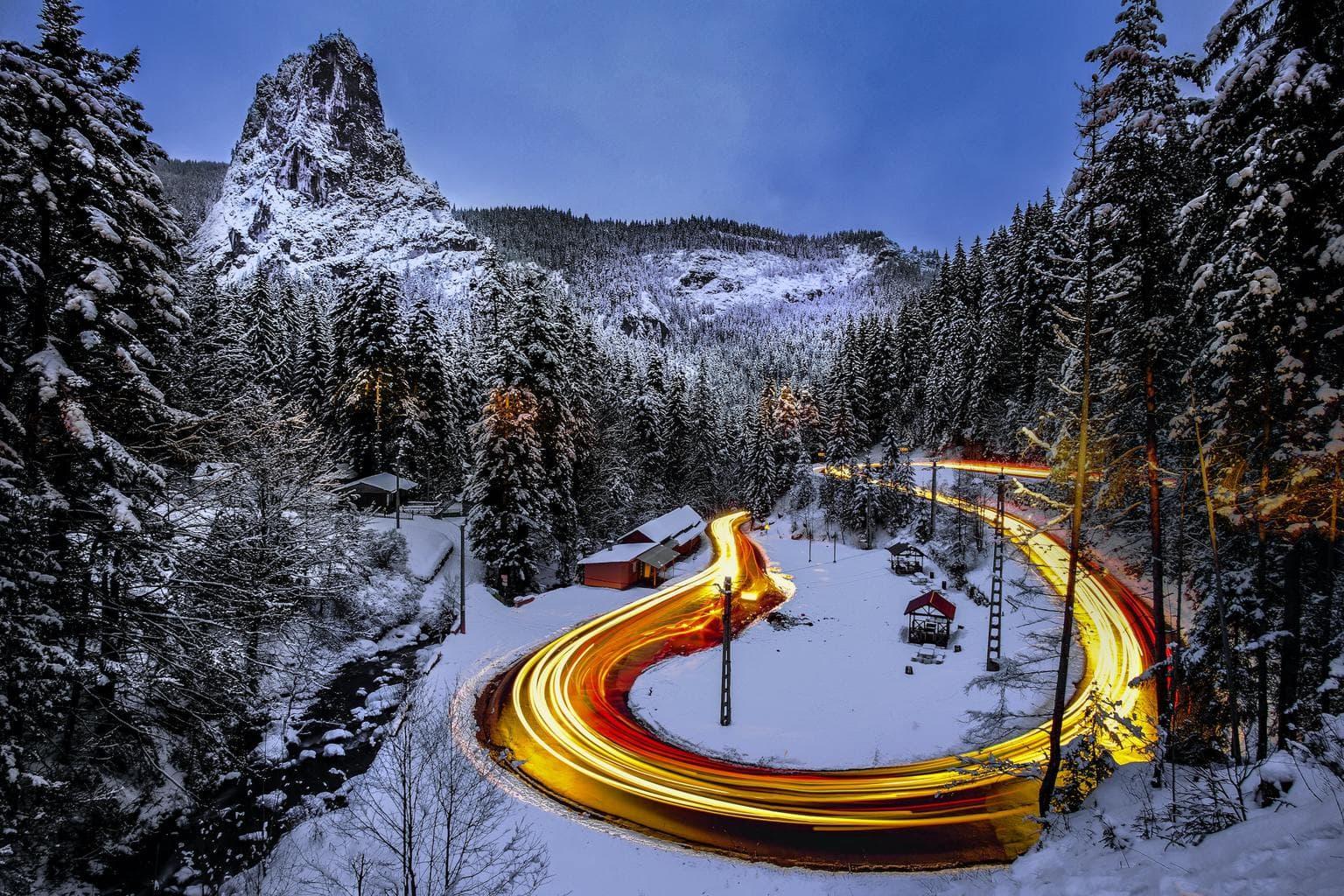 Paisaje de bosque nevado con estelas de luz de coches
