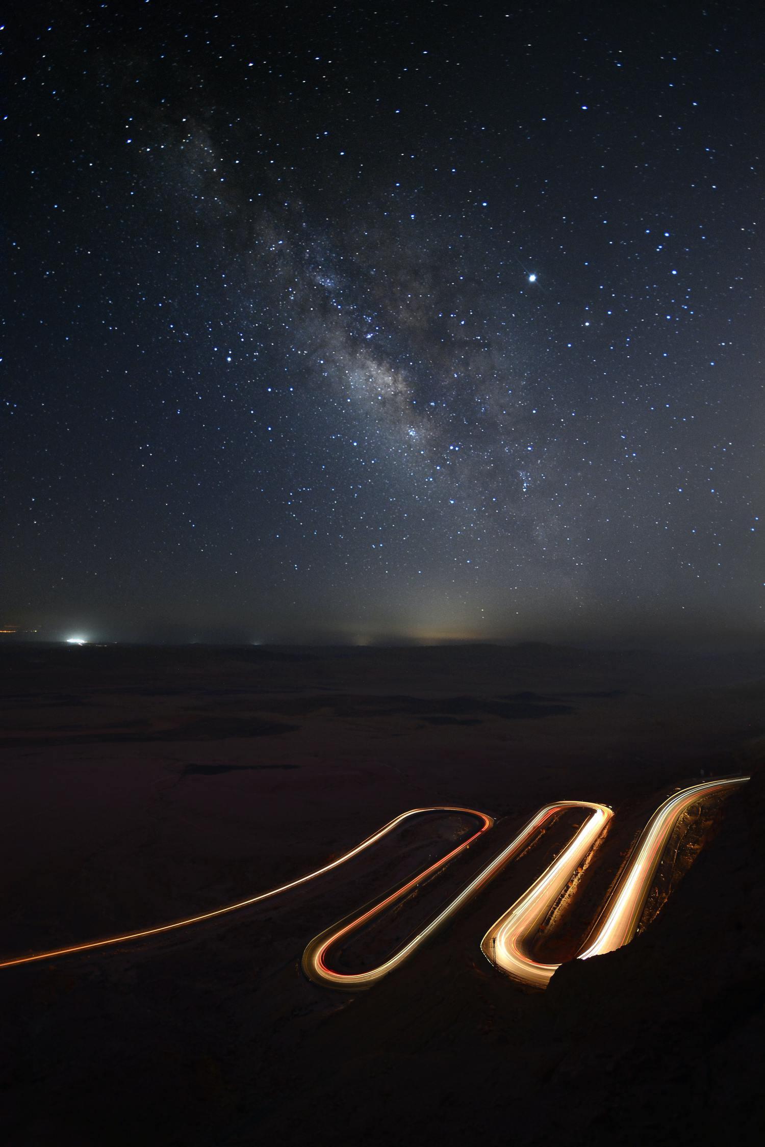 Foto de estelas del luz de coches con estrellas en el cielo