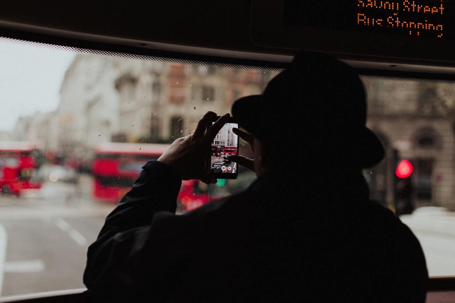 Hombre fotografiando la calle con un móvil desde el autobús