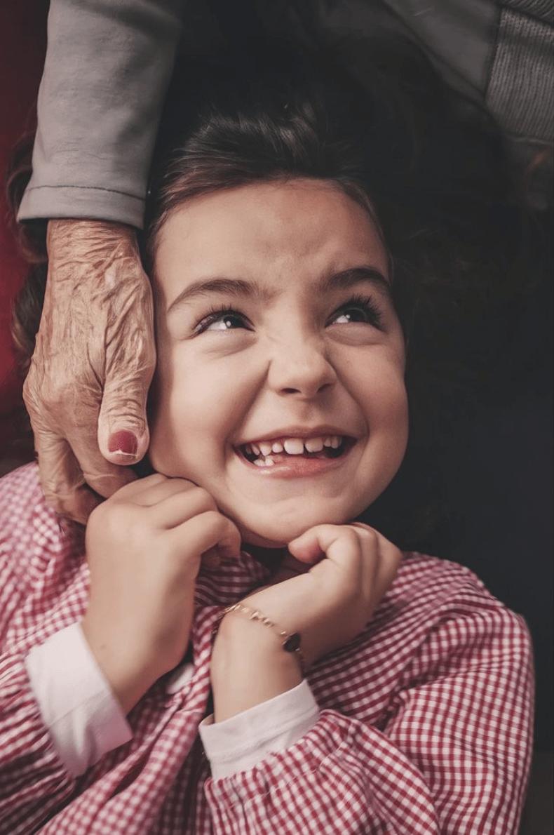 Niña sonriendo mientras la mano de la yaya le hace cosquillas en el cuello, ganadora del #fotoreto87 con el tema ternura