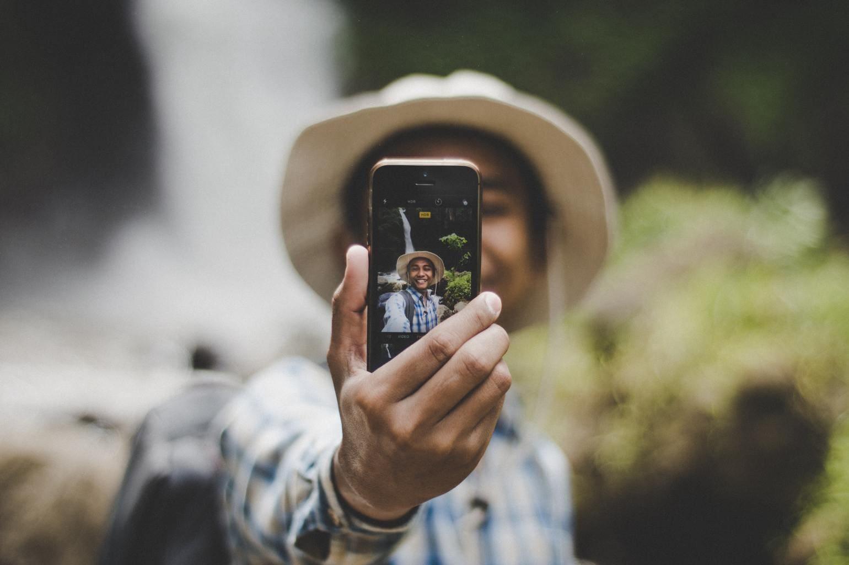 Chico haciéndose selfie con la cámara trasera del móvil.