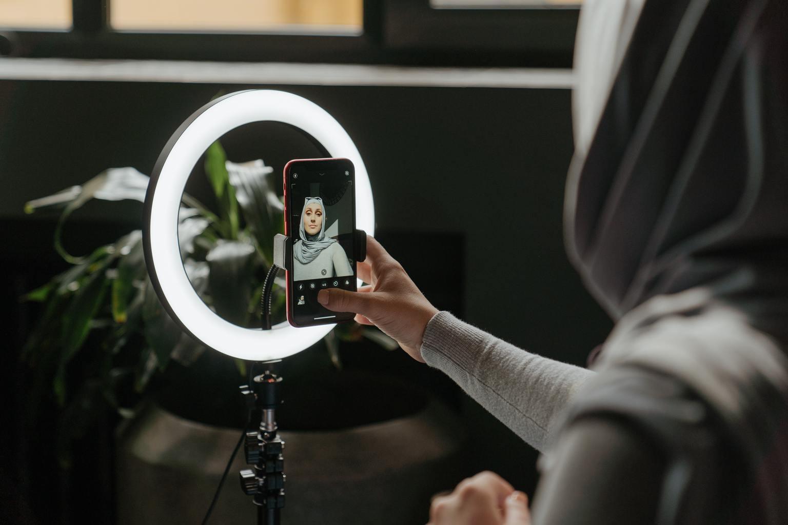 Mujer haciéndose selfie con anillo de flash tipo beauty dish para móvil