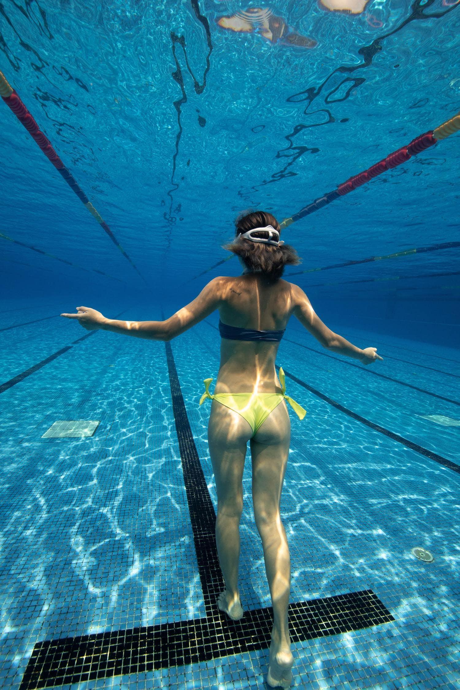Chica caminando en piscina debajo del agua