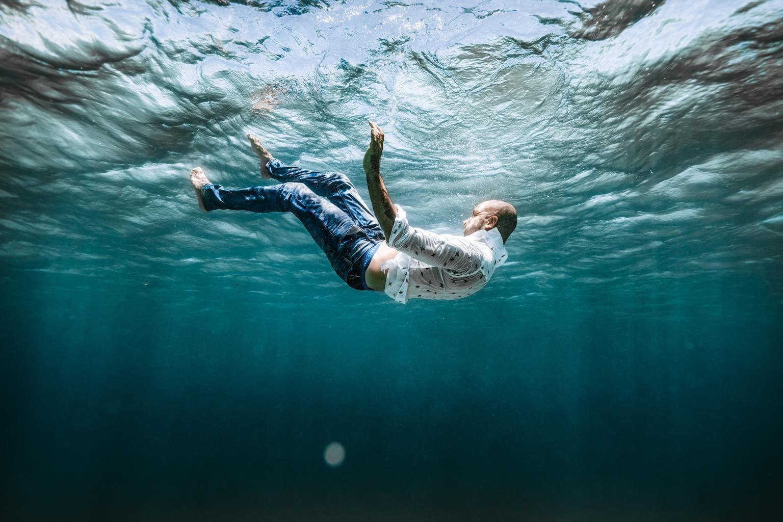Fotografía artística de hombre vestido debajo del agua