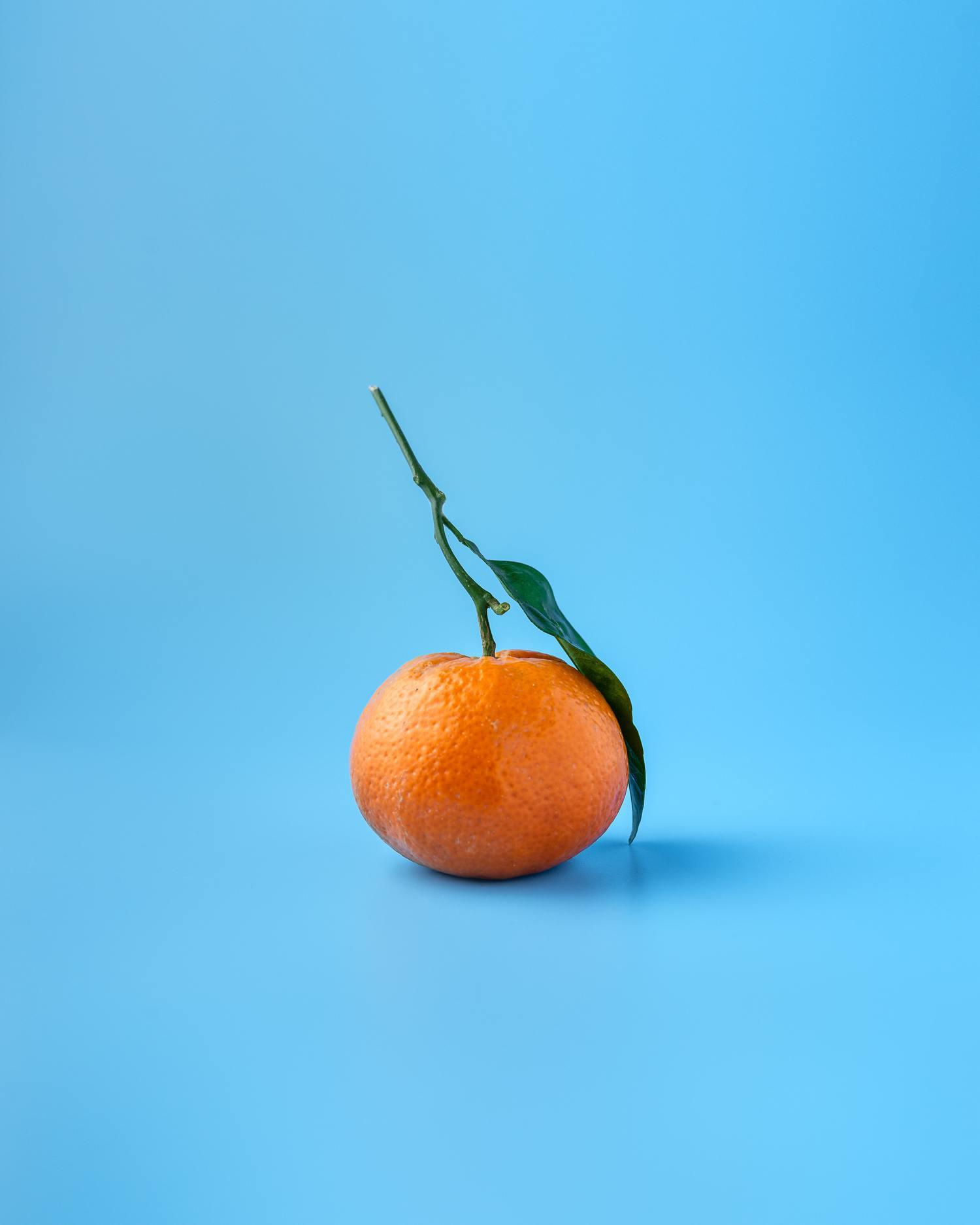 Fondo azul en contraste con mandarina naranja