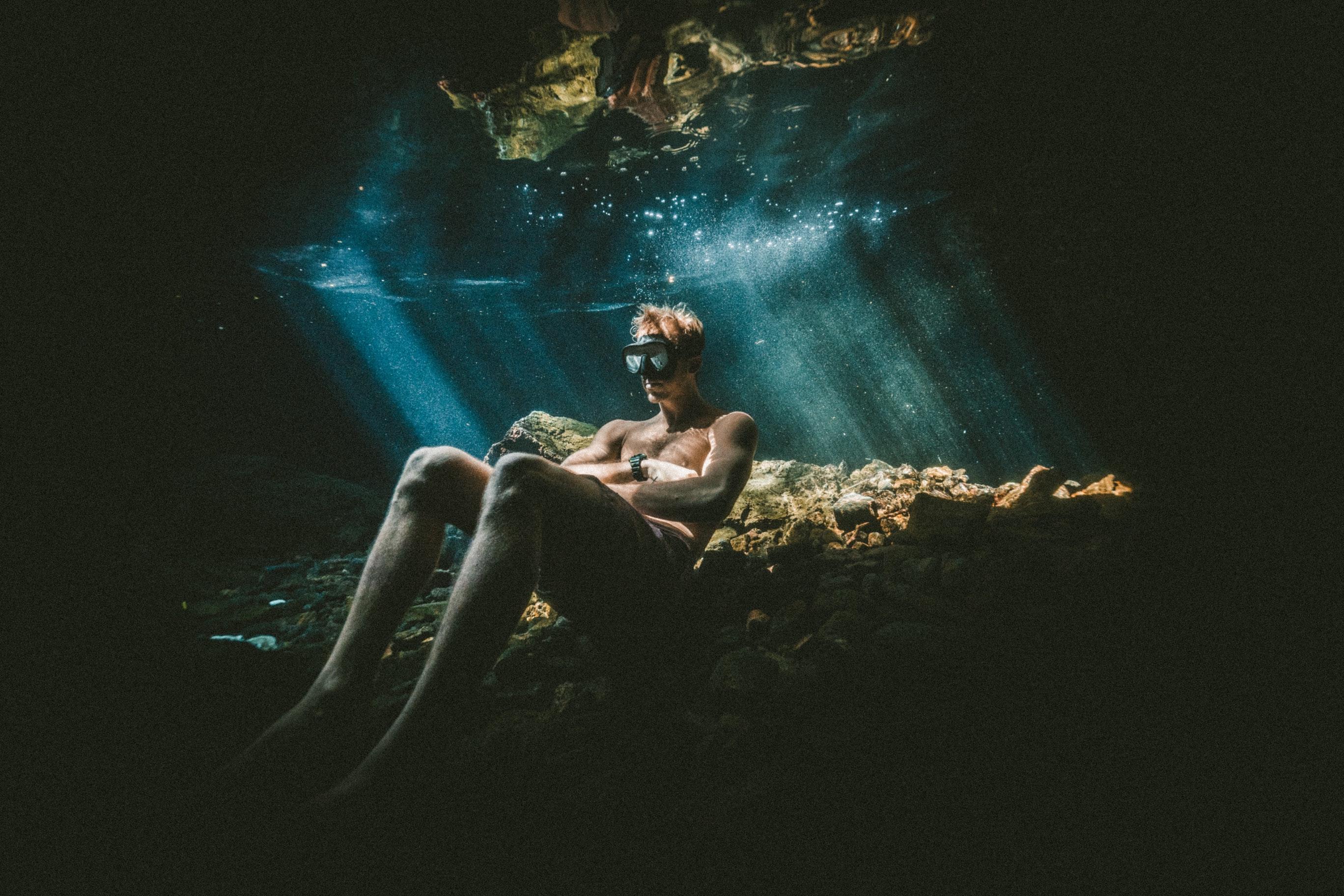 Hombre con gafas de buceo sentado en la roca debajo del agua