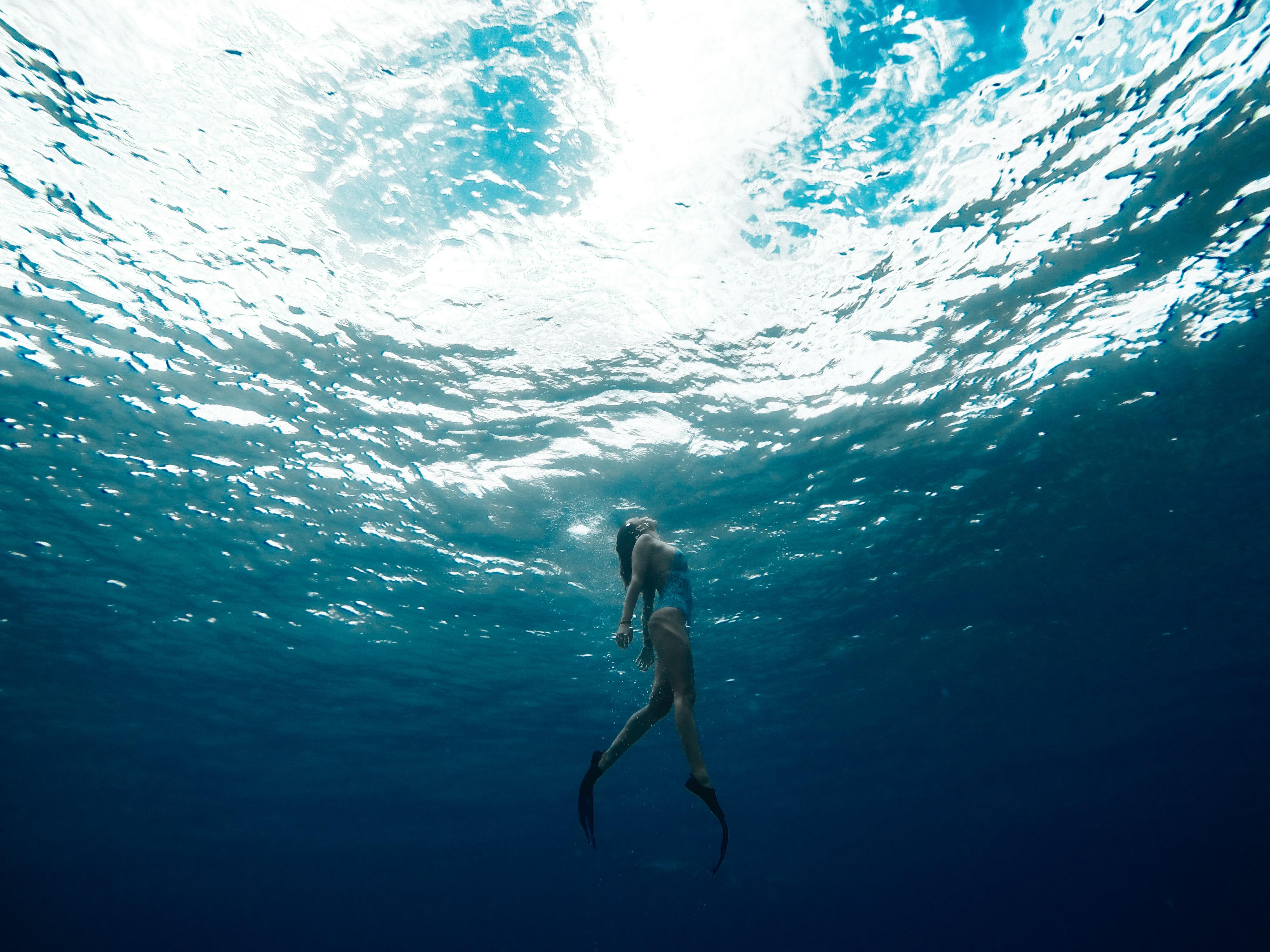 Mujer con aletas saliendo a la superficie