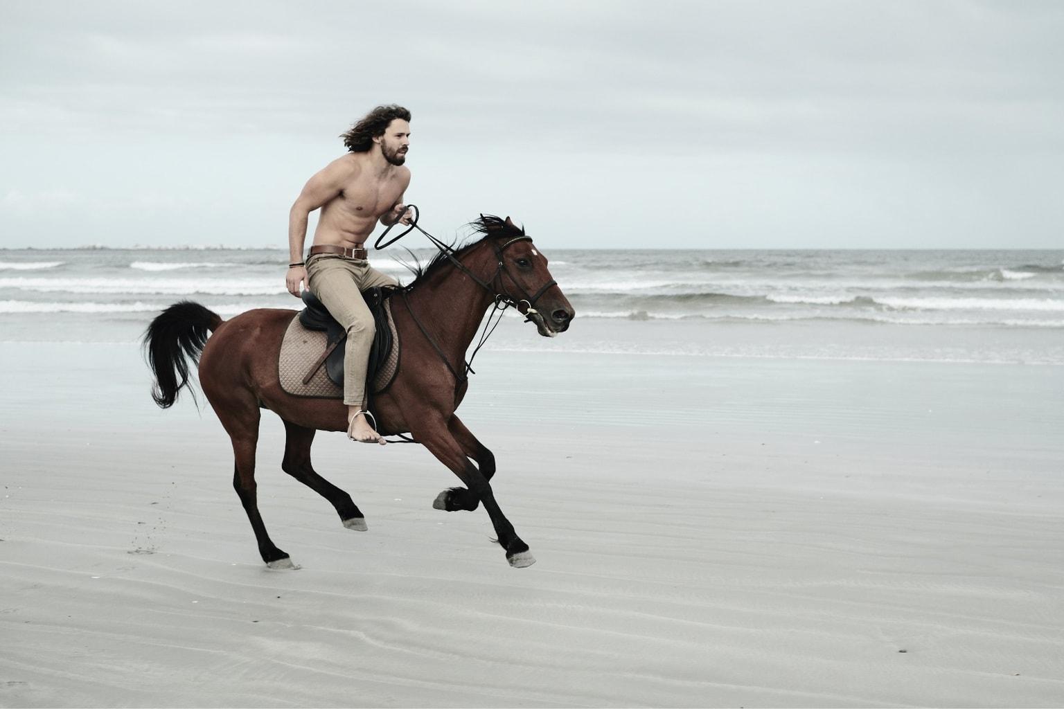 Hombre a caballo en la playa capturado por una Fujifilm X-T4