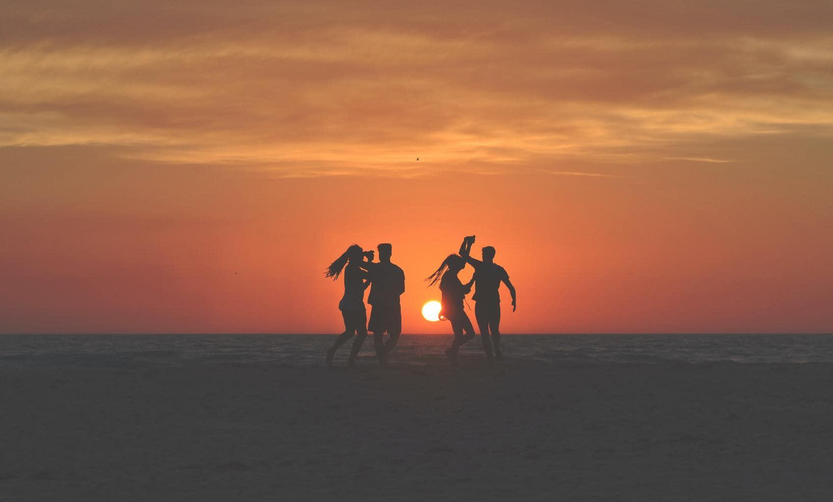 Siluetas bailando en la playa al atardecer para el fotoreto115 de vacaciones