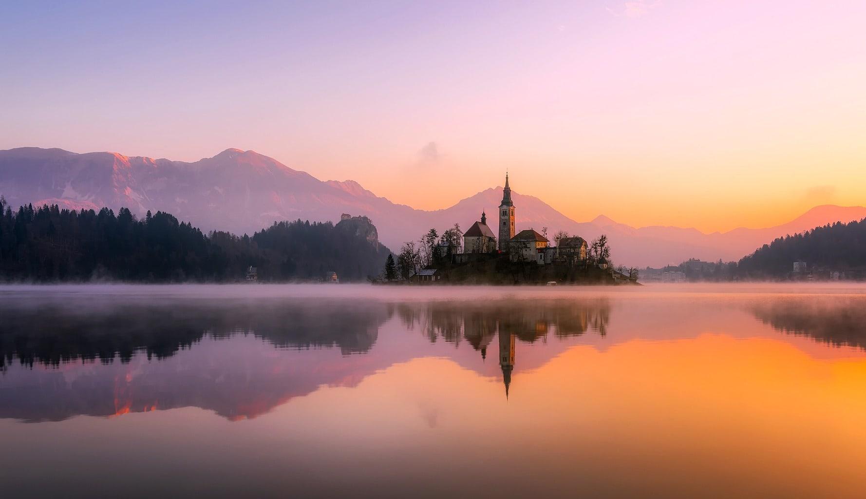 Panorámica de iglesia reflejada en lago con montañas al fondo