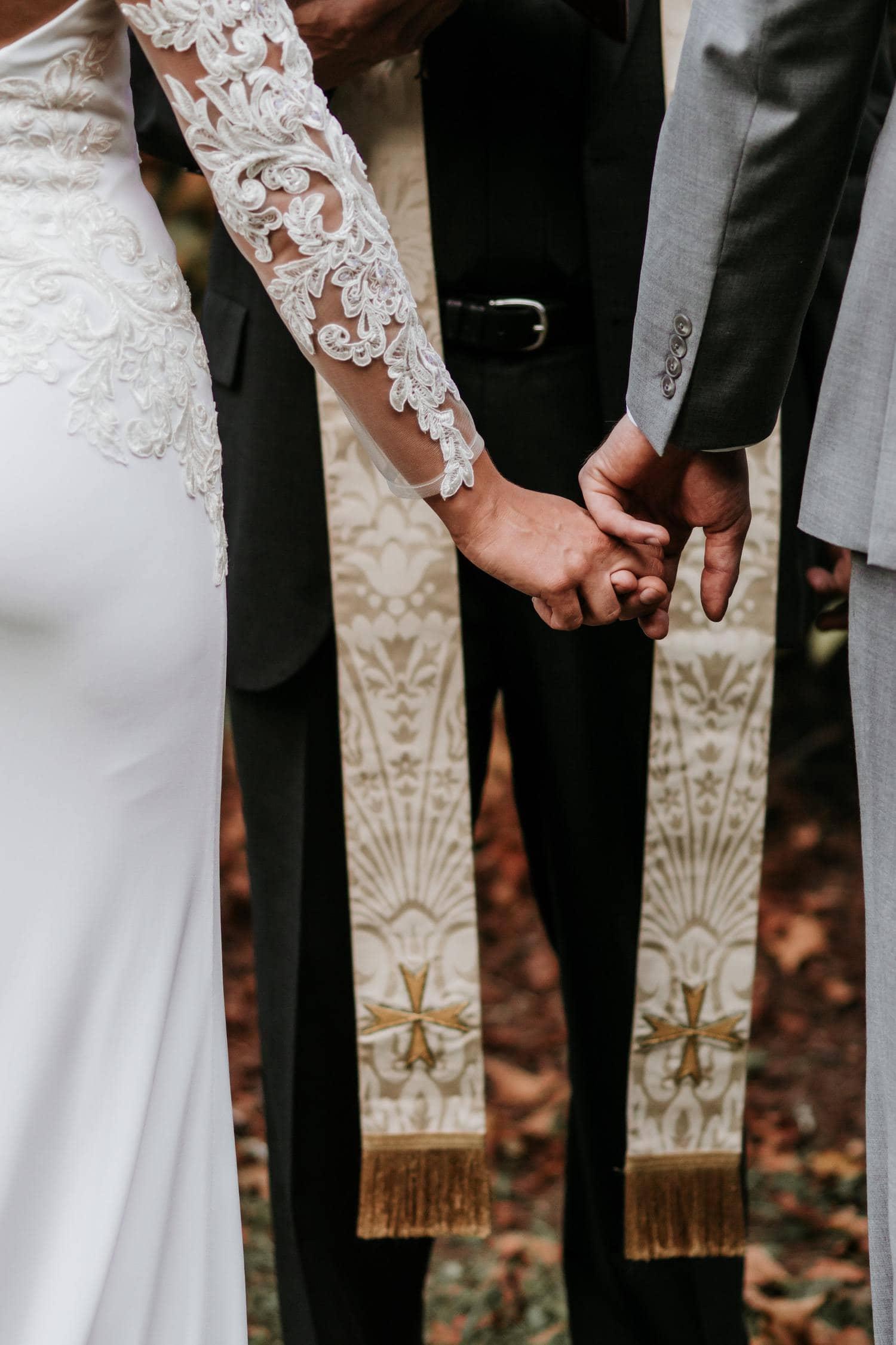 Manos entrelazadas de los novios en la boda
