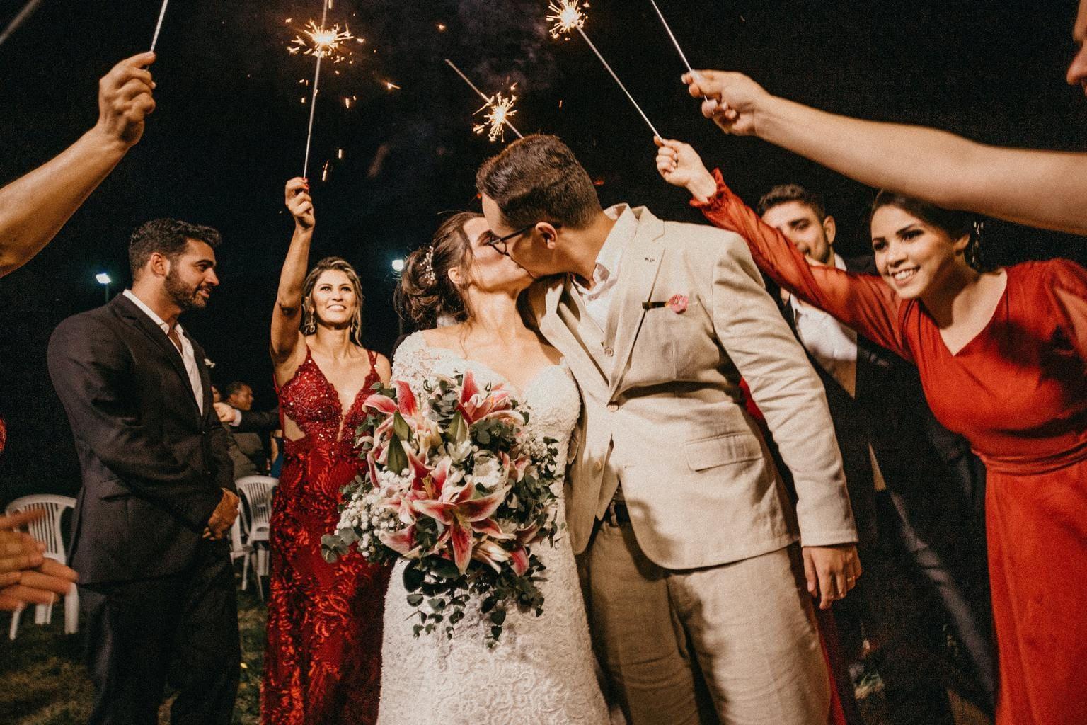 novios besándose bajo las bengalas de los invitados en el baile