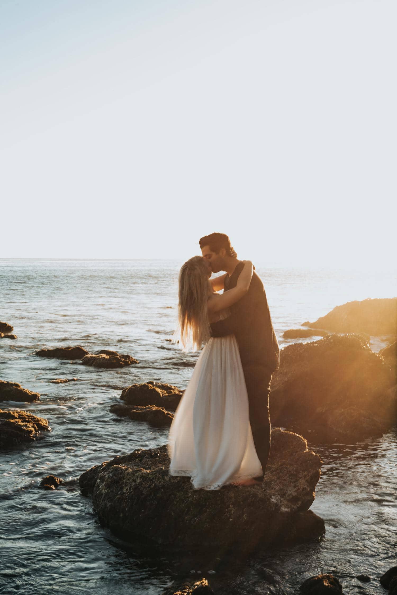 Novios besándose en roca junto al mar, sesión postboda